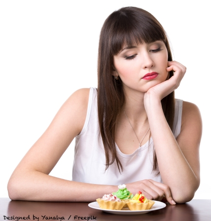 Young dieting woman sitting in front of plate with delicious cream tart cakes in dough baskets, looking at sweet dessert with unhappy and hungry expression, studio, white background, isolated